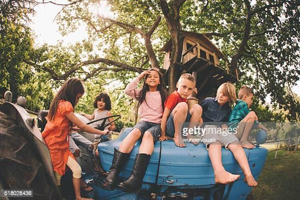 Asiatische Mädchen mit Freunden spielen auf einem alten Traktor