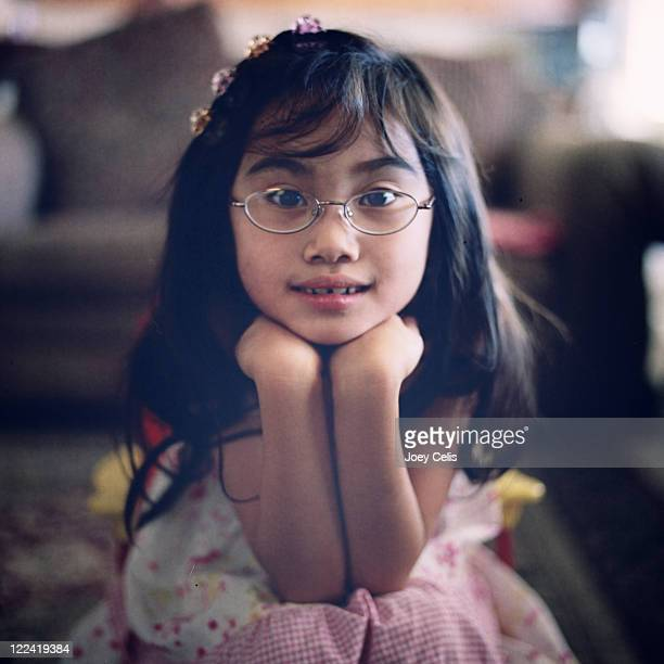 Asian girl with glasses rest her head on her hands