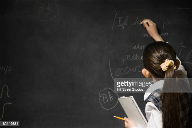 Asian girl writing on blackboard