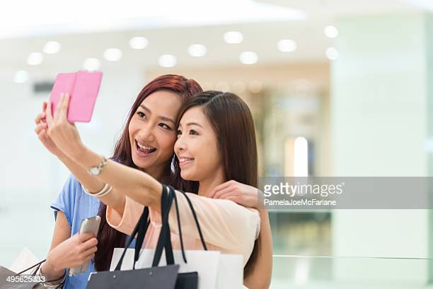 Asian Girlfriends Posing for a Selfie in a Shopping Mall