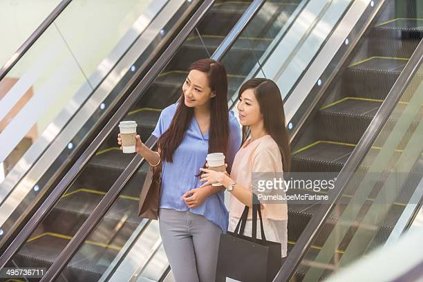 Asian Girlfriends Riding Escalator and Drinking Coffee