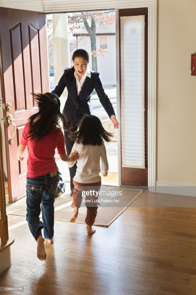 Asian girls greeting mother in doorway