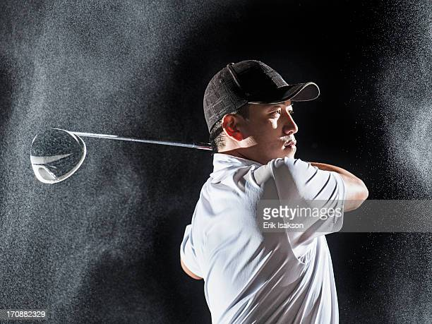 Asian golf player swinging club in rain
