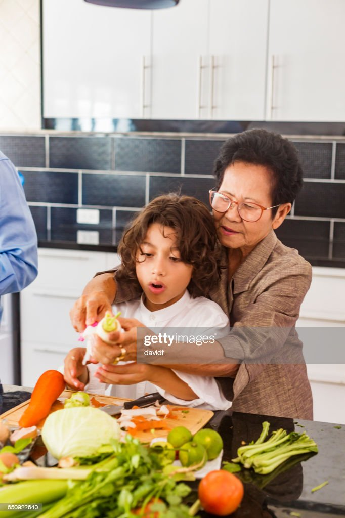 Asian Grandmother Showing Grandson How to Cook Healthy Thai Food : Foto stock