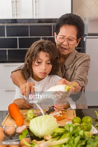 Asian Grandmother Showing Grandson How to Cook Healthy Thai Food : Stock Photo