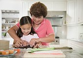 Asian grandmother teaching granddaughter to make sushi hand roll