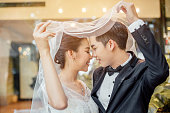 Asian groom and Asian bride are under viel together and are about to kiss each other with a smiling and happy face.
