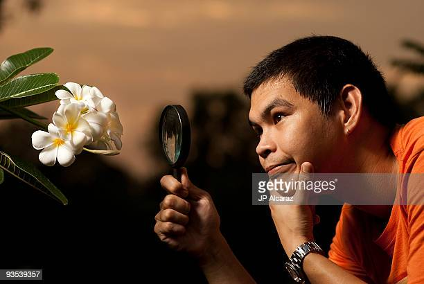 Asian guy checking flower with magnifying glass