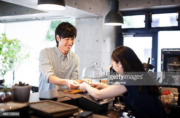 Asian guy paying in a cafe