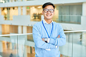 Waist up portrait of cheerful Asian businessman wearing glasses smiling happily at camera standing at glass balcony in modern office building, copy space