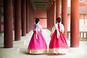 Asian Korean woman dressed Hanbok in traditional dress walking in Gyeongbokgung Palace in Seoul, South Korea.