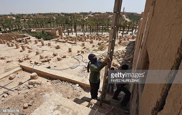 Asian laborers restore an old building in the historical UNESCO World Heritage Atturaif district on the outskirts of Riyadh on July 13 which is part...