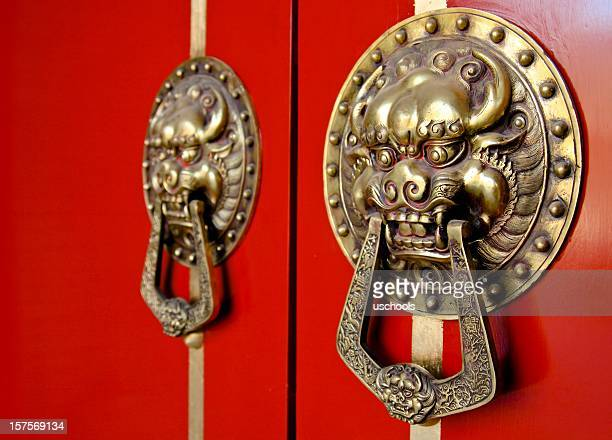 Asian Lion Door Knockers on Red Gate