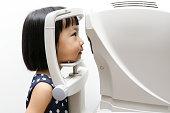 Asian Little Chinese Girl Doing Eyes Examination Through Auto refraktometer in isolated White Background