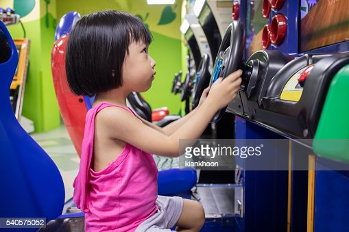 Asian Little Chinese Girl Playing Arcade Game Machine : Stock Photo