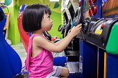 Asian Little Chinese Girl Playing Arcade Game Machine at a indoor Amusement Playground
