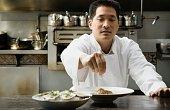 Asian male chef seasoning food