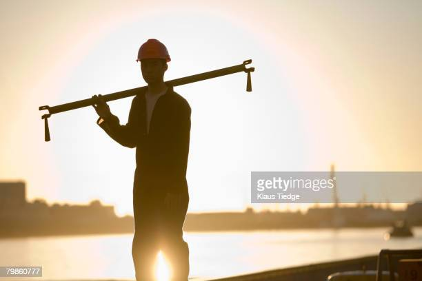 Asian male dock worker holding pipe