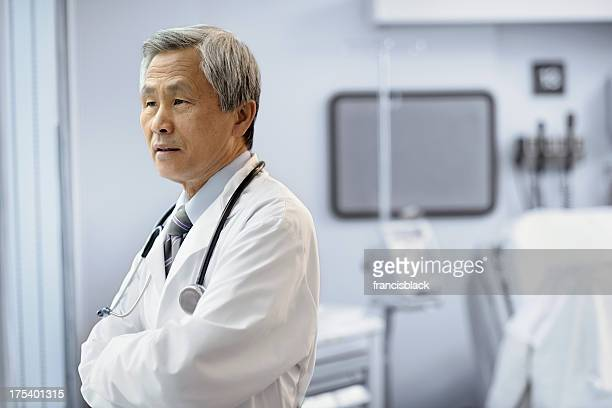 Asian male doctor looking out hospital room window.