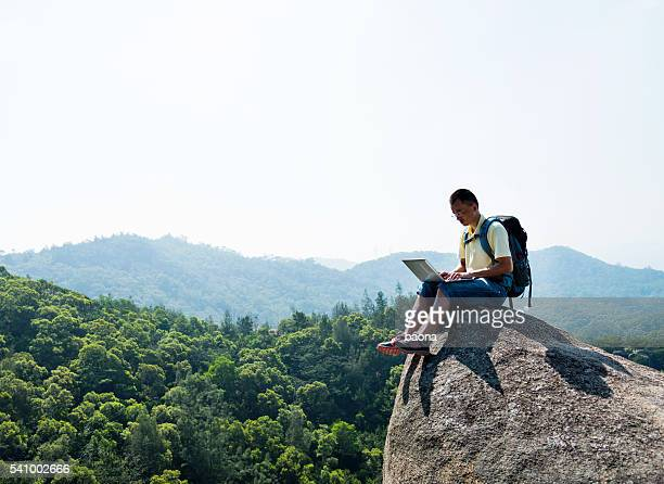 Asian male hiker using laptop on rock