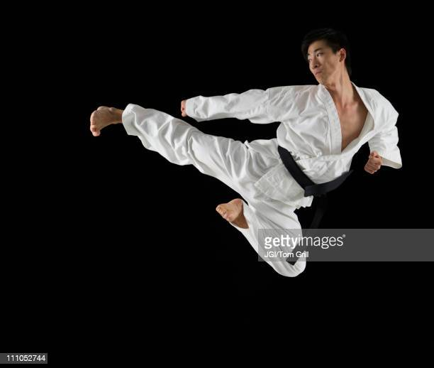 Asian male karate black belt kicking in air