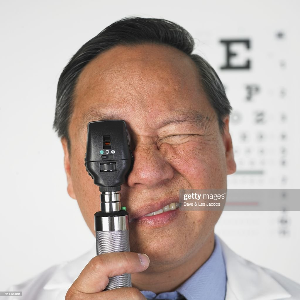 Asian male optometrist looking through medical instrument : Stock Photo