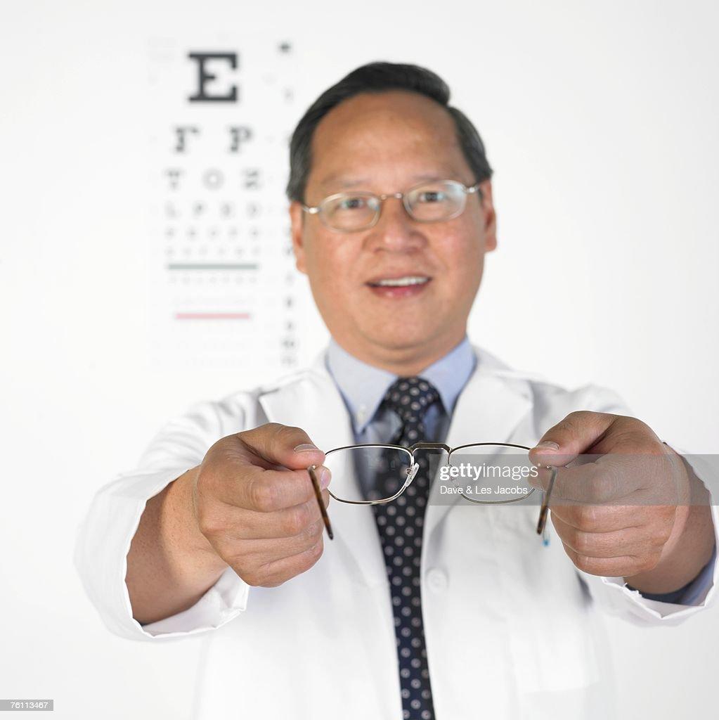 Asian male optometrist offering eyeglasses : Stock Photo