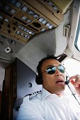 Asian male pilot in cockpit of airplane