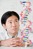 Asian male scientist looking at DNA model