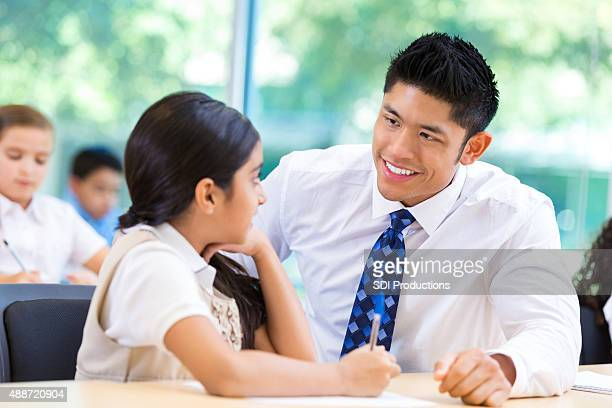 Asian male teacher talking with elementary school girl in classroom