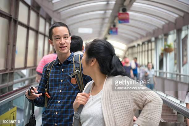 Asian Man and Woman Riding Escalator