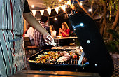 Asian man are cooking for a group of friends to eat barbecue