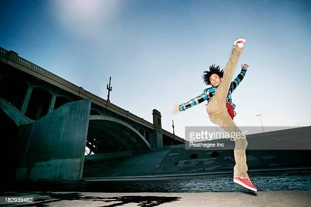 Asian man break dancing under overpass