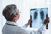Asian man doctor diagnose patient x-ray  radiography film, asian medical concept