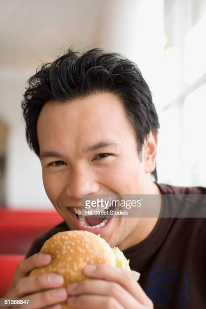 Asian man eating hamburger