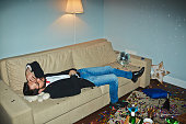 Asian man in jeans and jacket having nap in messy living room after wild New Year party