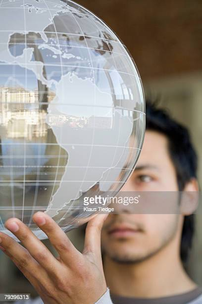 Asian man holding globe