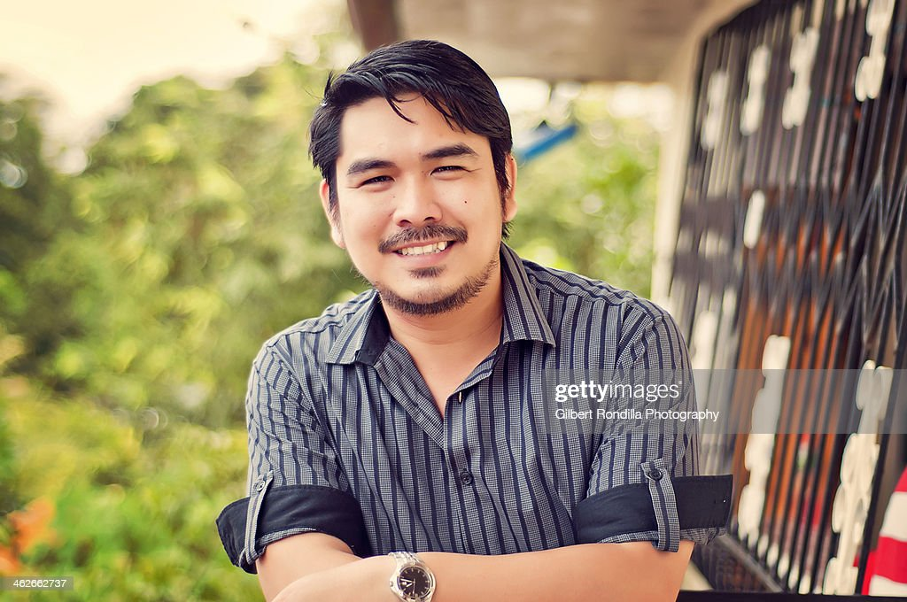 Asian man in black striped shirt