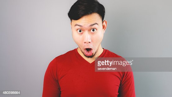 Asian man in red T-shirt is feeling surprised and shocked. : Stock Photo