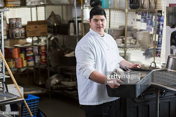 Asian man in restaurant carrying tub of dirty dishes