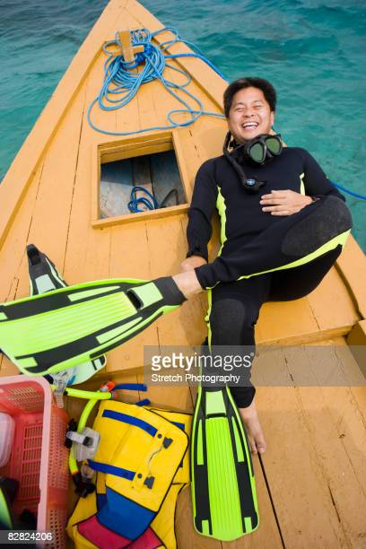 Asian man in scuba gear on boat deck