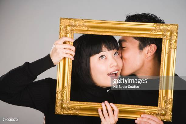 Asian man kissing girlfriend inside picture frame