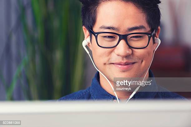 Asian man listening to music with headphones