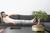 Asian man looking at bonsai tree