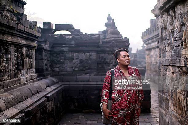 Asian man looking at carving at Borobudur temple