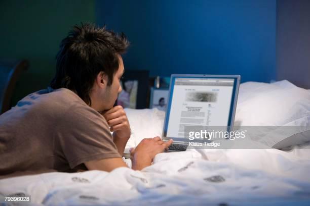 Asian man looking at laptop