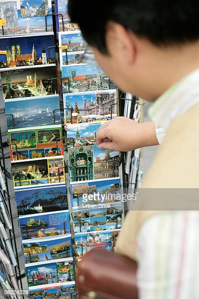 Asian man looking for a postcard in a rack, selective focus