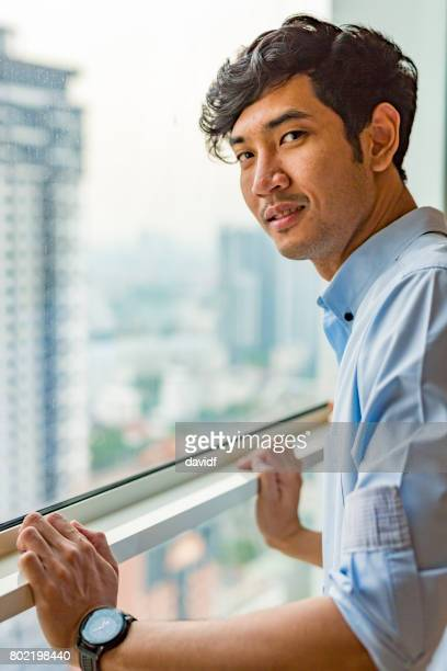 Asian Man Looking Out a Window
