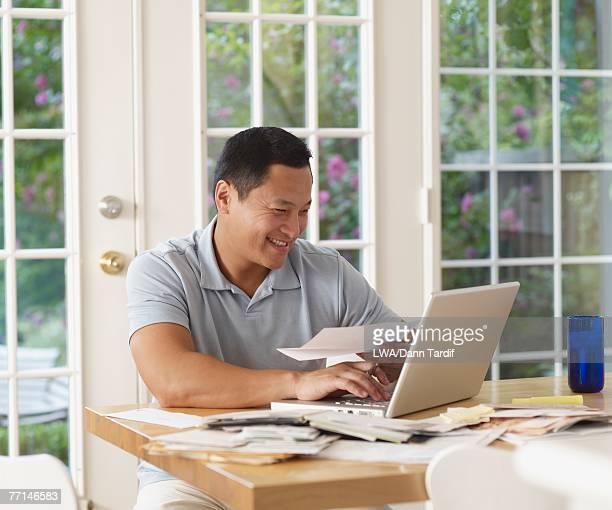 Asian man paying bills online