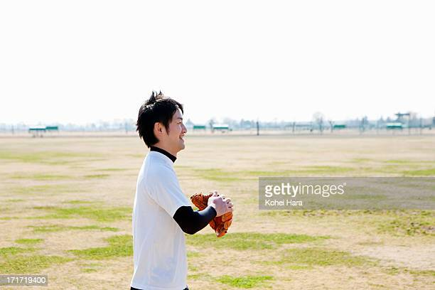 asian man playing baseball